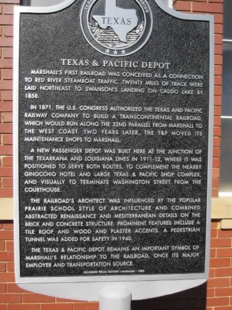 Historical Marker about the Texas & Pacific (T&P) Depot in Marshall Texas ... Marshall's first railroad was conceived as a connection to Red River steamboat traffic. Twenty miles of track were laid northeast to Swanson's Landing on Caddo Lake by 1858. In 1871, the U. S. Congress authorized the Texas & Pacific Railway Company to build a transcontinental railroad, which would run along the 32nd parallel from Marshall to the West Coast. Two years later, the T&P moved its maintenance shops to Marshall. A new passenger depot was built here at the junction of the Texarkana and Louisiana lines in 1911-12, where it was positioned to serve both routes. To complement the nearby Ginocchio Hotel and huge Texas & Pacific shop complex, and visually to terminate Washington Street from the Courthouse. The railroad's architect was influenced by the popular prairie school and combined abstracted renaissance and Mediterranean details on the brick and concrete structure. Prominent features include a tile roof and wood and plaster accents. A pedestrian tunnel was added for safety in 1940. The Texas & Pacific depot remains an important symbol of Marshall's relationship to the railroad, once its major employer and transportation source. Recorded Texas Historic Landmark - 1985